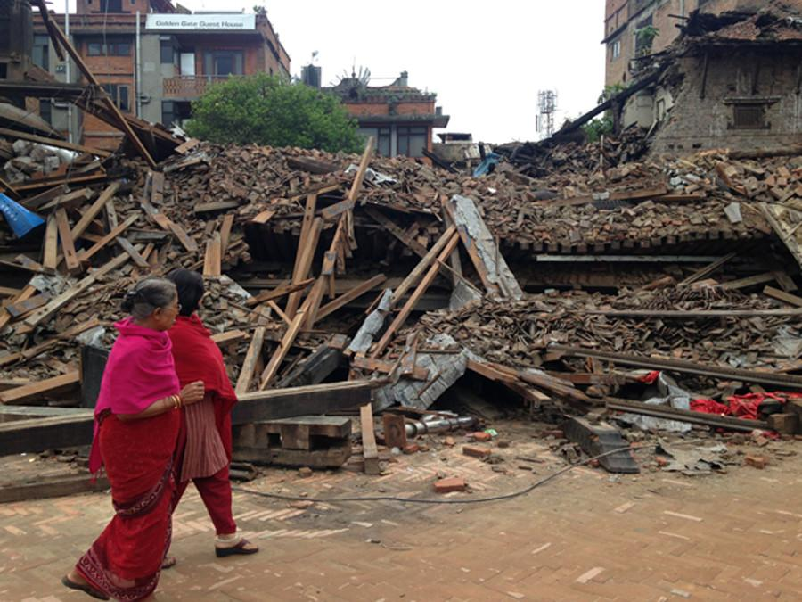Two+women+walking+past+a+destroyed+building+in+Bhaktapur%2C+Nepal.