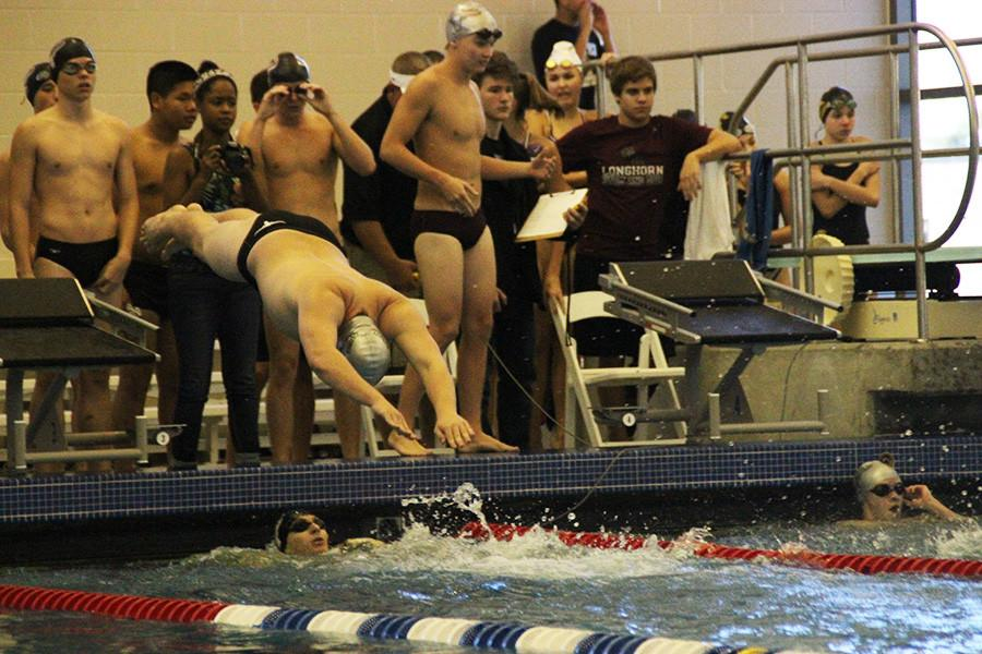 Varsity swimmer leaps from the blocks to put his relay farther ahead.