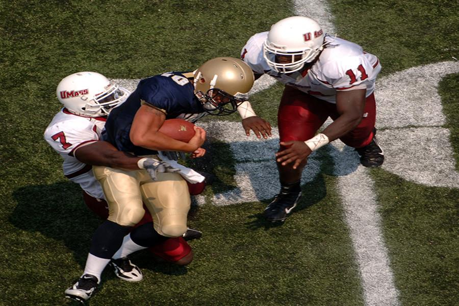 060909-N-9693M-010 Annapolis, Md. (Sept. 9, 2006) - Navy Quarterback Kaipo-Noa Kaheaku-Enhada is tackled by Massachusetts defensive back James Ihedigbo, #7, and linebacker Charles Walker, #11. The Navy Midshipmen (2-0) triumphed over the UMass Minutemen (1-1) 21-20. U.S. Navy photo by Damon J. Moritz (RELEASED)