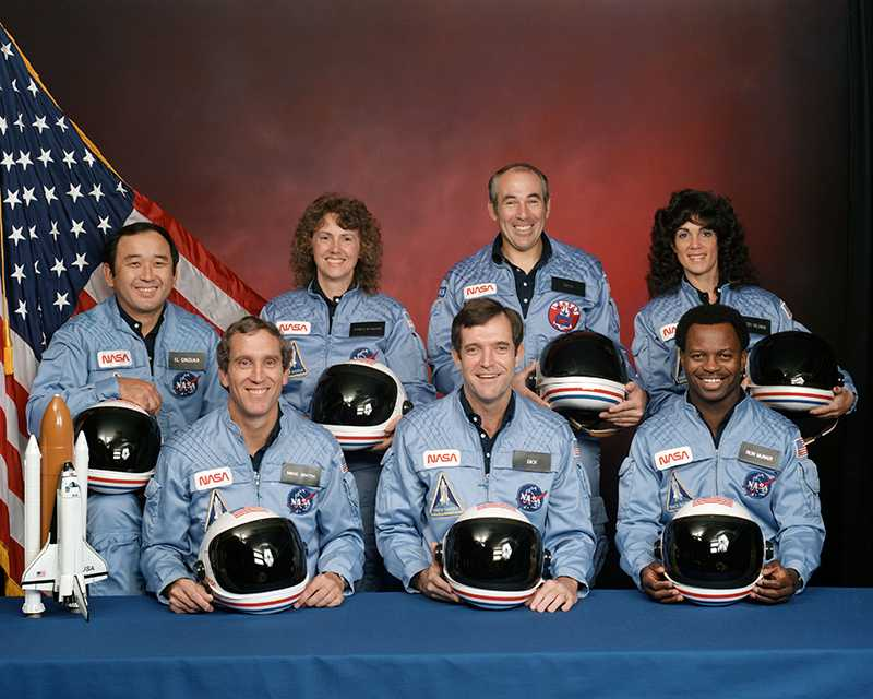 The Challenger Crew.  In the back row from left to right: Ellison S. Onizuka, Sharon Christa McAuliffe, Greg Jarvis, and Judy Resnik. In the front row from left to right: Michael J. Smith, Dick Scobee, and Ron McNair.