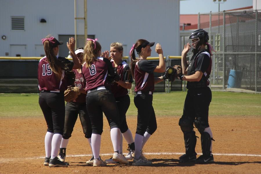 The team huddles to encourage each other before the inning begins.