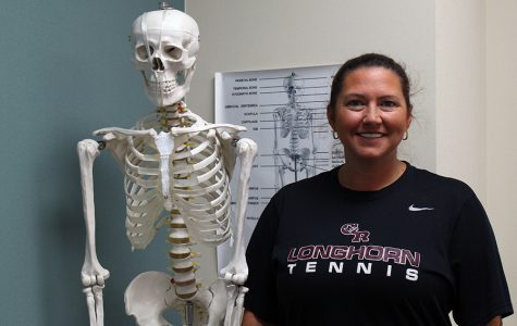 Ms. Raley standing next to Bob the skeleton.