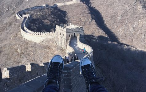 Ally Walters feet dangling over The Great Wall of China