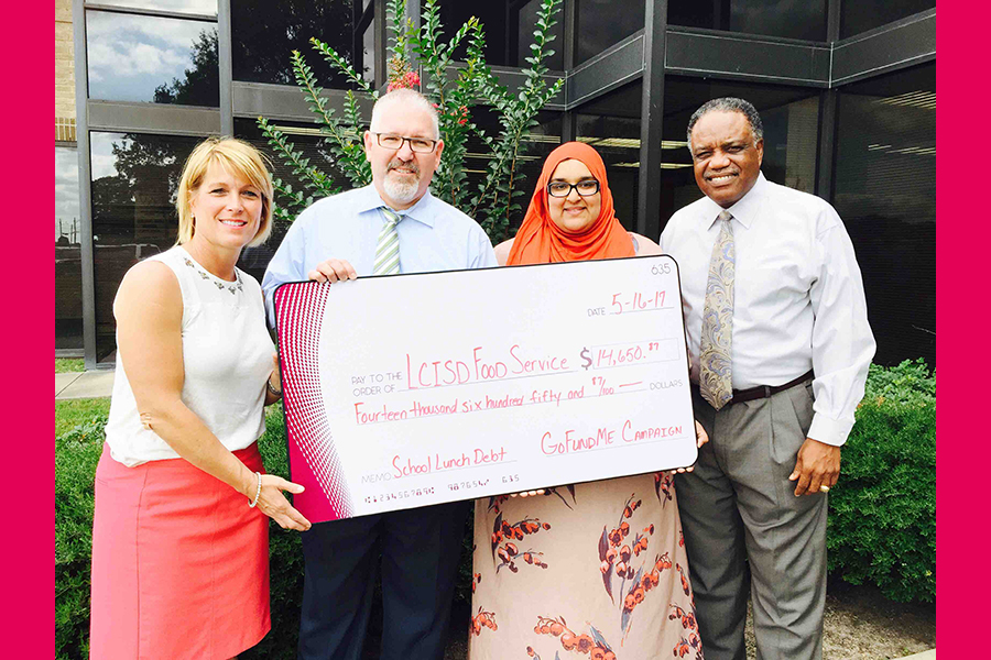 Amina Ishaq and other members holding their check to wipe LCISD lunch debt