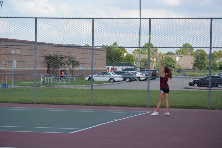 Lauren Caples tosses the ball to serve.