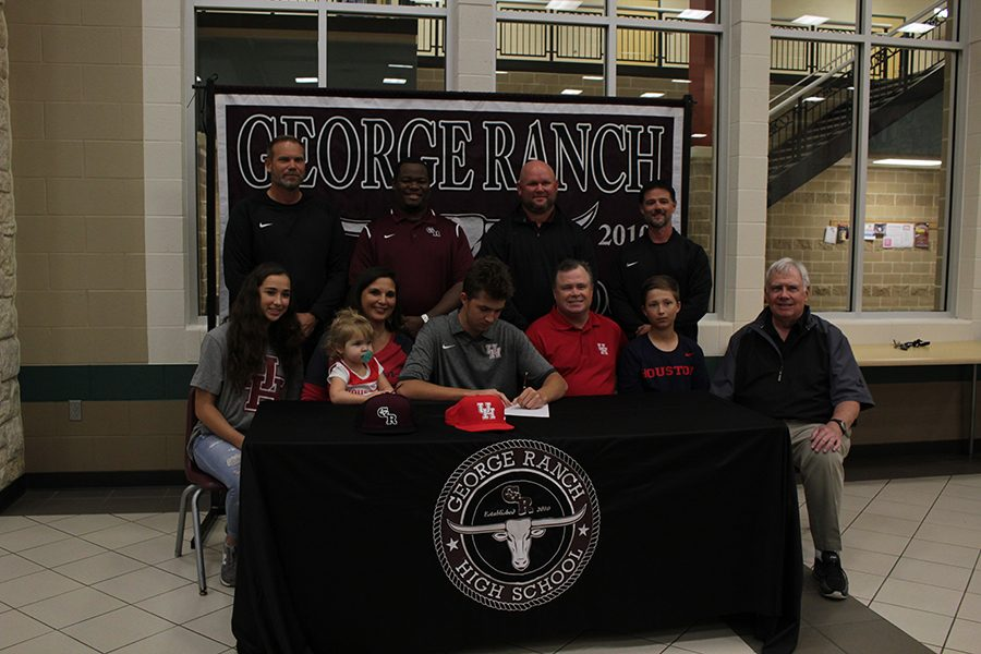 Cole McMillan sits with his family and coaches as he signs his way into collage.