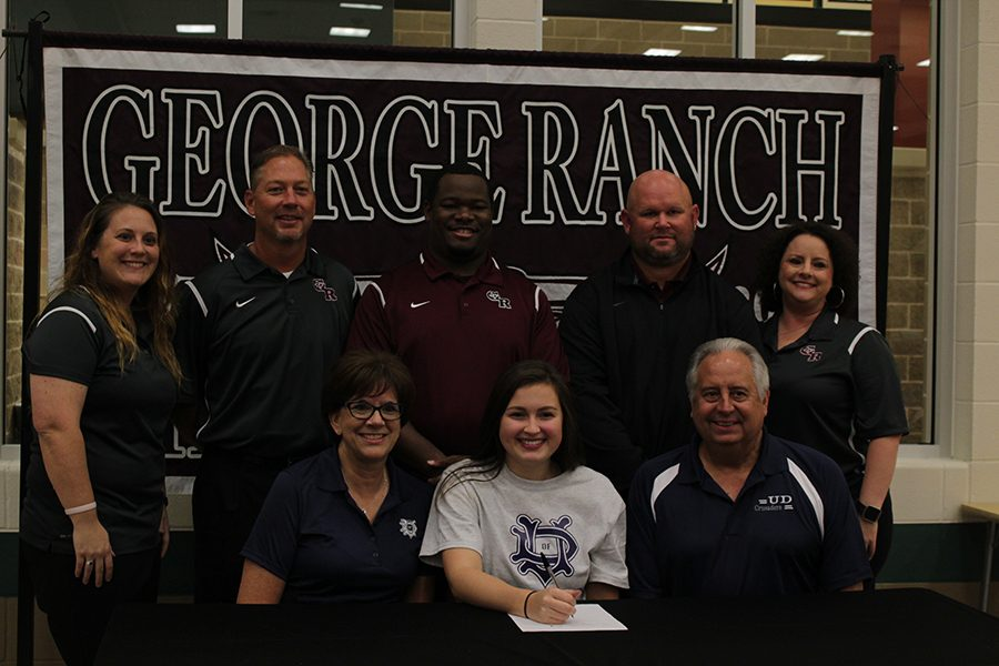 Lexie Shafer signs with her collage for volleyball.