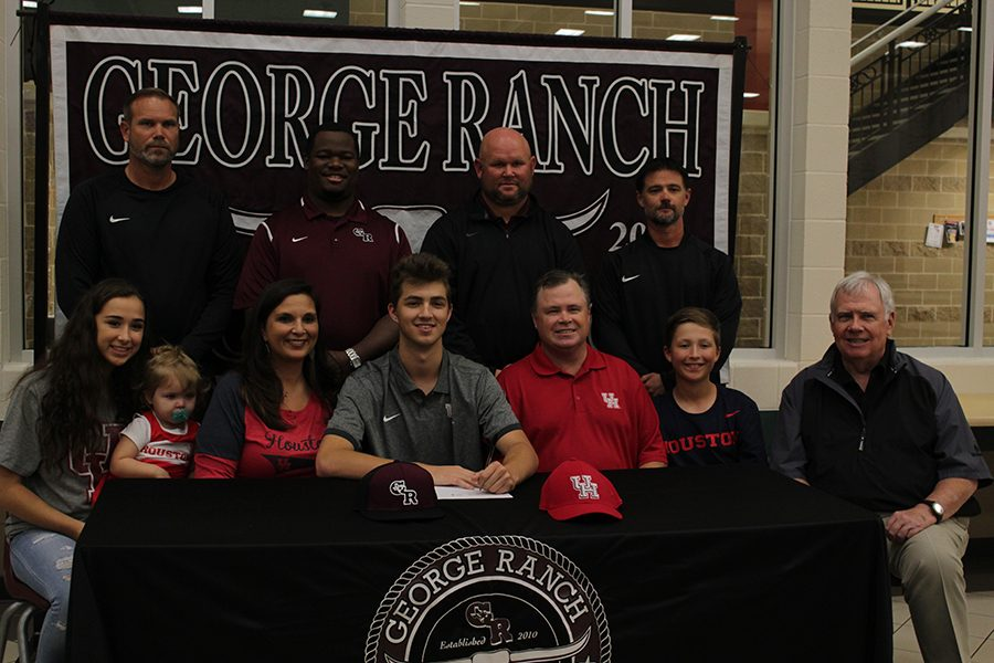 Cole McMillan with his coaches and principal.