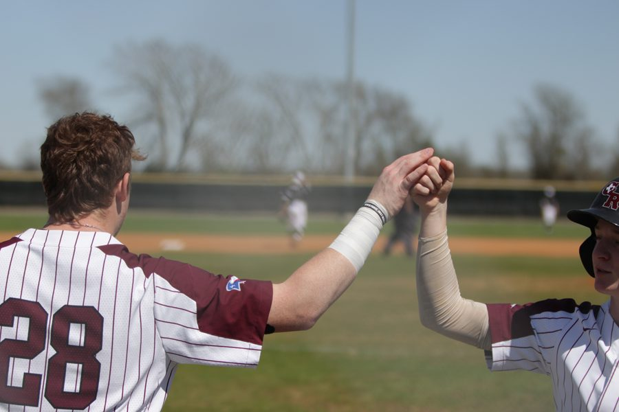 DH Joseph Menefee congratulates PR Fisher Byers after he touches home plate