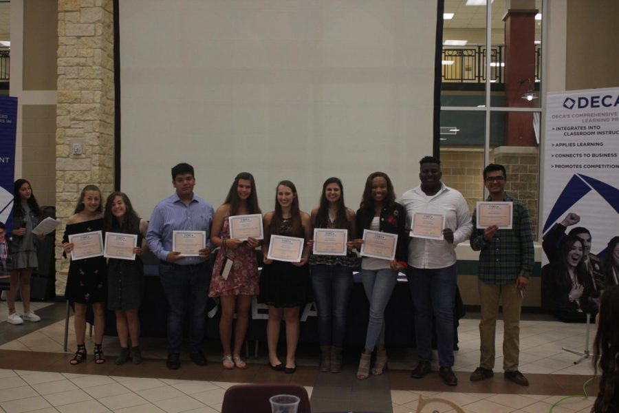 DECA member awarded with certificates of service.