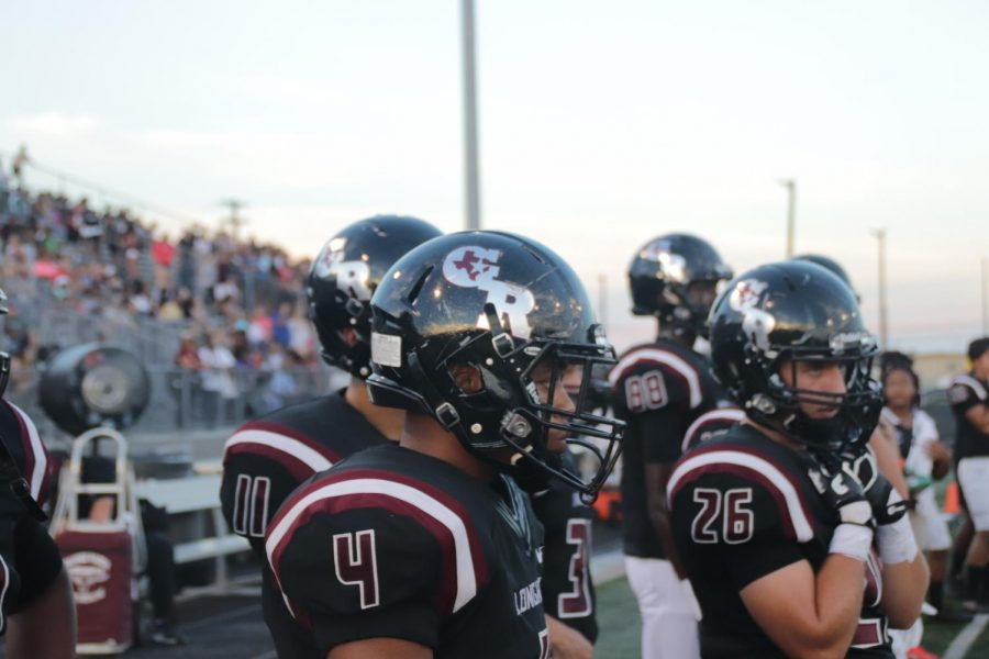 T Mcgee(12) stands on the sideline as the defense hold the field.
