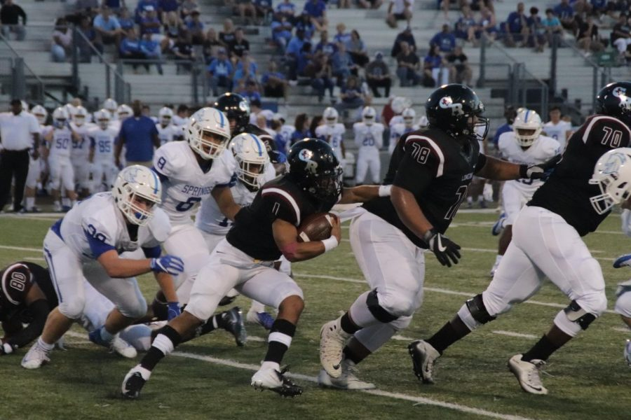 Jayren Miller(12) on the run behind his linemen looking for an open hole.
