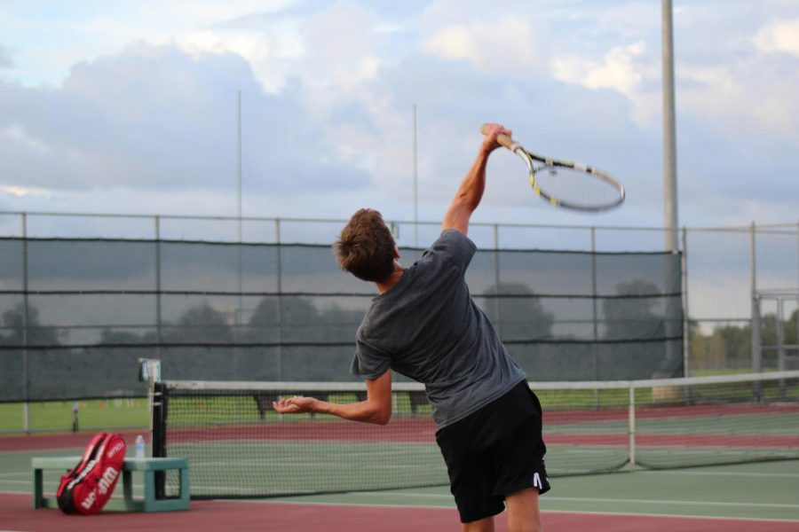 Tyler Gray (9) serving the ball.