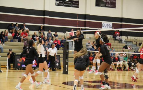The varsity volleyball team jumping for glory.