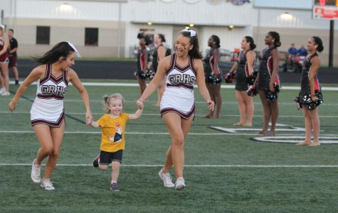 Two Lady Longhorns and a coach's daughter running along the field after the football players, preparing for the game.