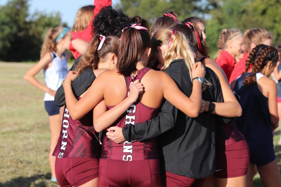 The varsity team in huddle to motivate each other and hype each other up before the race.