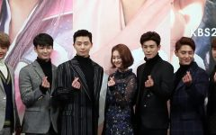 The cast of Hwarang, consisting of numerous famous idols and actors, pose for heart picture at a conference.