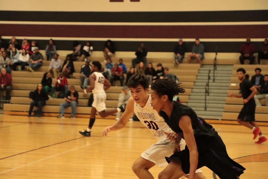 Caden Cook (11) running to defend and block the shot