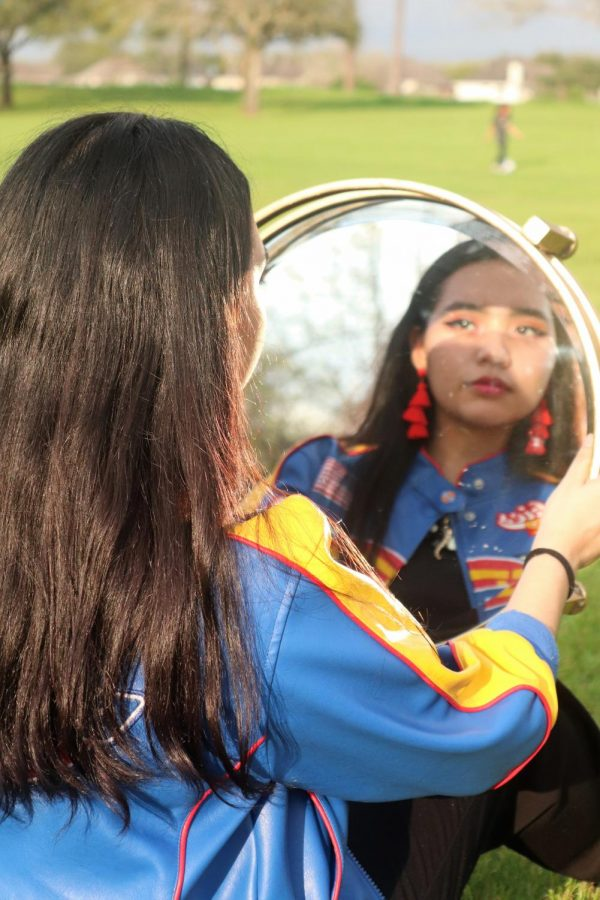 The mirror creates a sense of depth within the picture.