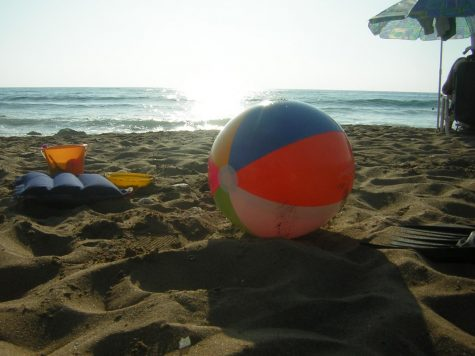 A beach ball is resting peacefully with the sun behind it on the beach.