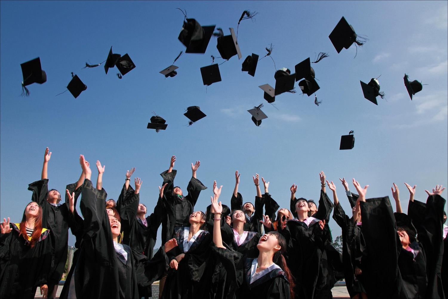 Seniors are celebrating the fact that they just graduated by throwing their caps in the air.