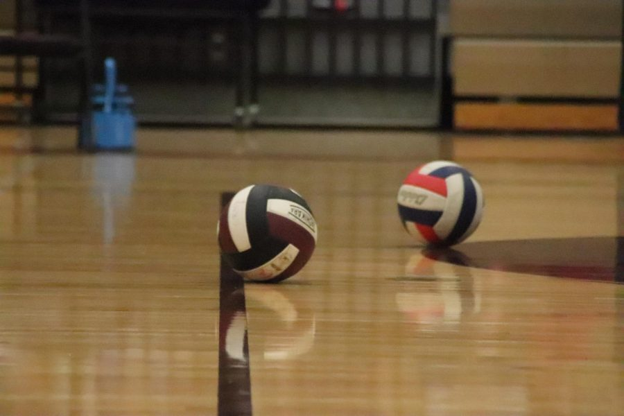 Two volleyballs sitting on the ground