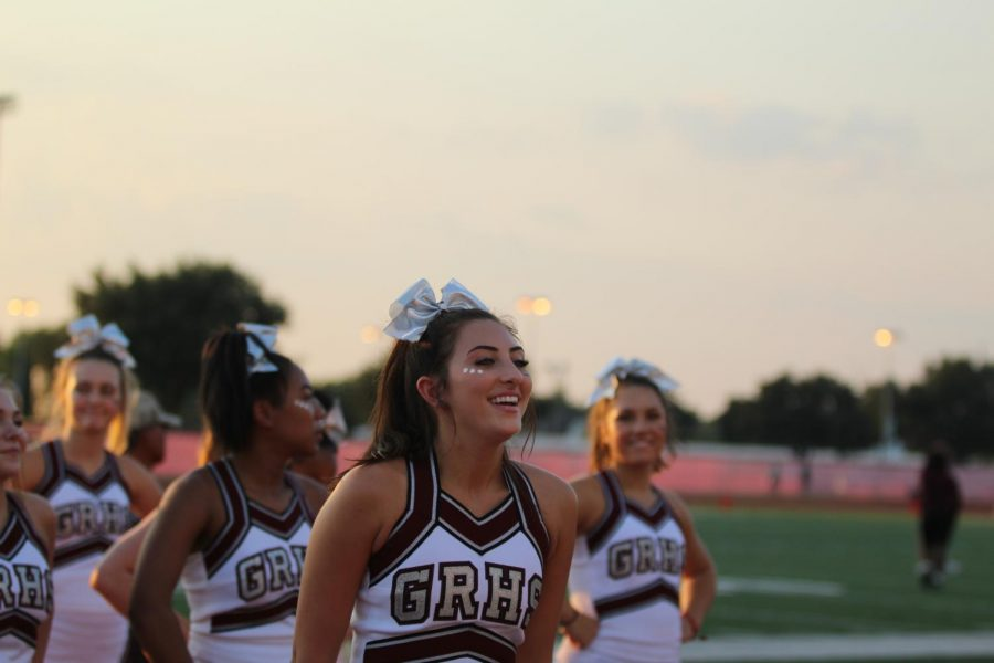 Senior captain Jenna Christoffel leading fellow cheerleaders in a sideline dance