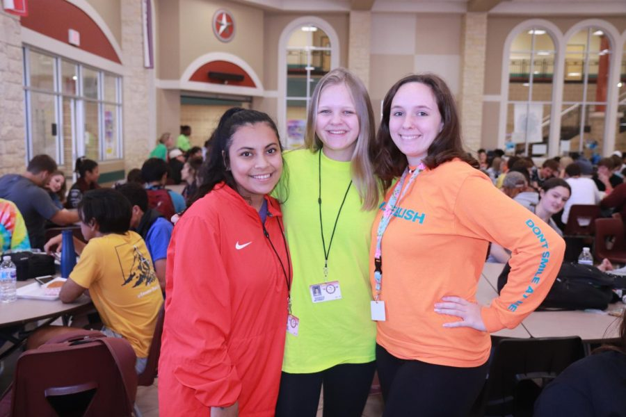 Nohemi Avalos (11), Mia Fineman (11), and Lylian Tharp (11) posing with their bright neon, highlighter like, colored shirts.