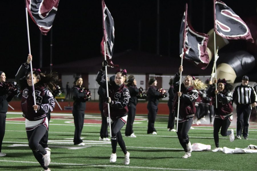 Cheerleaders, Jenna Christoffel(12), Averi Glaze(12), Brooke Heitkamp(10), and Myla Williams(10), run with the GRHS flags to kick off the second half after half time.