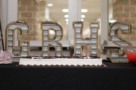 A nice table set up with the celebratory cake and fruit punch in front of letters that spell GRHS.