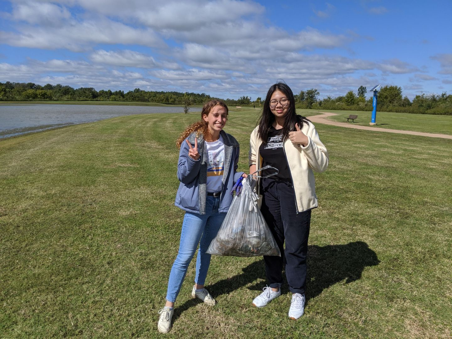 Ave Breeze(on the left) and a participate in the tree huggers club spend their saturday morning picking up trash at the sugarland park.