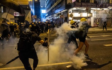 Hong Kong police and protesters clash in the midst of a tear gas haze.