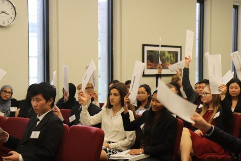 """Delegates"" hold up their placards as they agree to a 15-minute caucus."
