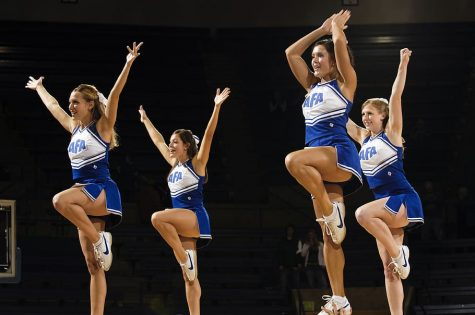 These four college competitive cheerleaders perform to the crowd while in a stunt.
