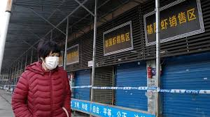 A Man with a mask walking the empty streets of Wuhan.