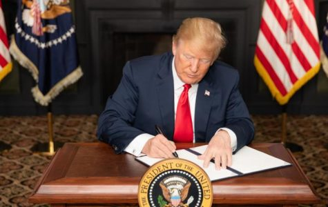 President Donald Trump signing documents to reimpose sanctions on Iran.
