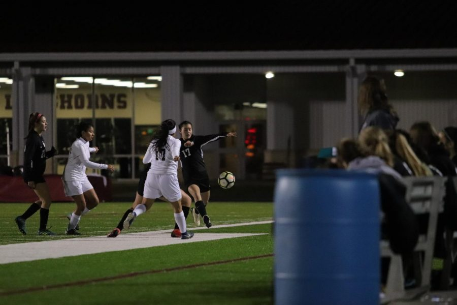 Cassidy Hoang (17) kicking the ball while the rest of the team is on the side lines.