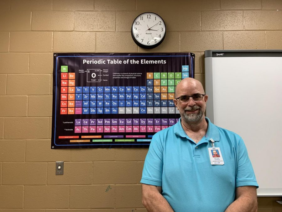 Mr. Sherman, a new science teacher, posing at his Periodic Table poster.
