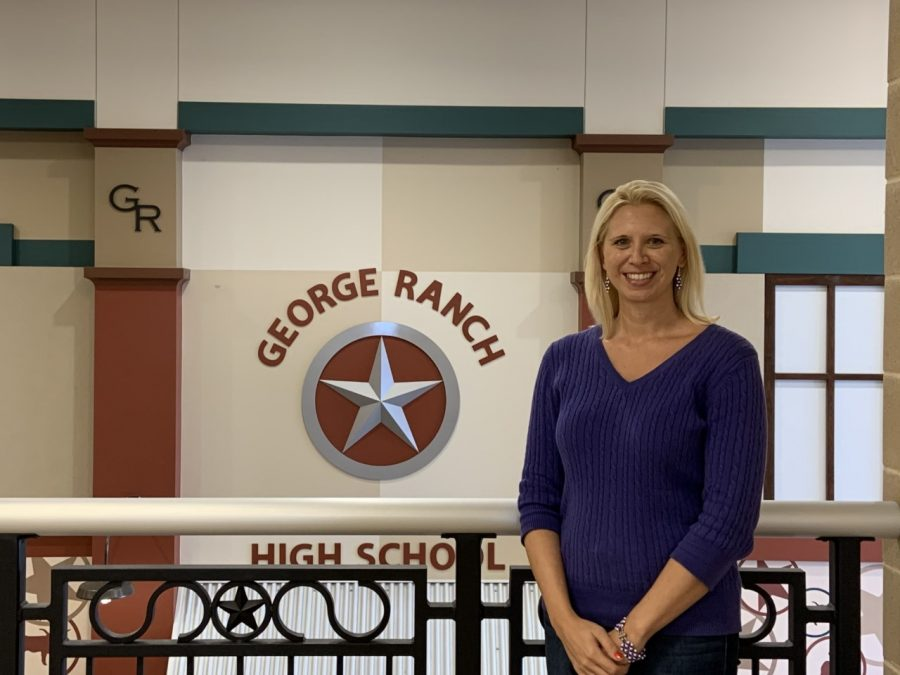 Mrs.+Hunt+proudly+standing+in+front+of+one+of+the+George+Ranch+signs.+She+strives+to+make+her+students+feel+like+they+can+be+themselves.