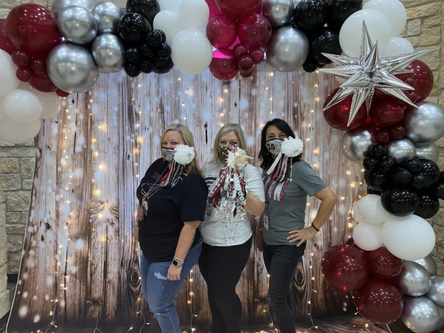 Mrs. Thomas, Mrs. Patterson, and Mrs. Moreno pictured posing in front of the pop up photo op in the main hallway.