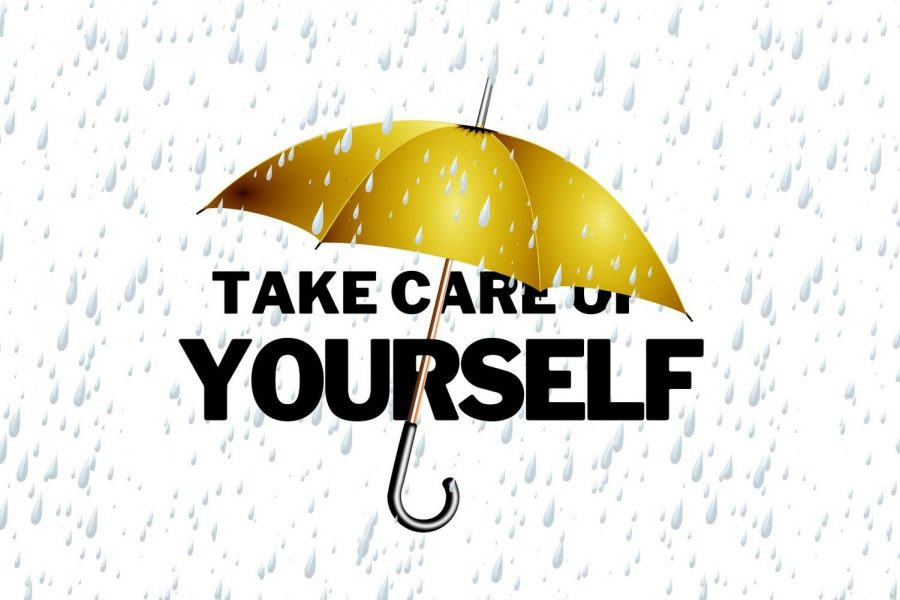 The golden umbrella has the words take care of yourself written behind it because self-care is important.