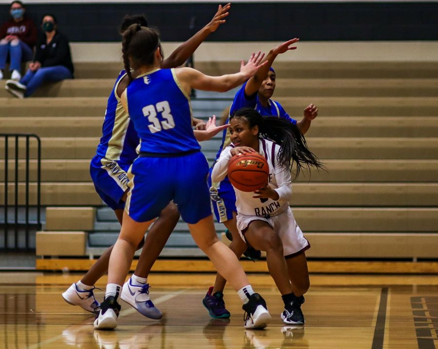 No. 3 Savannah Velasquez (11) using her height as an advantage to dribble the ball under and through Elkins' defensive team.