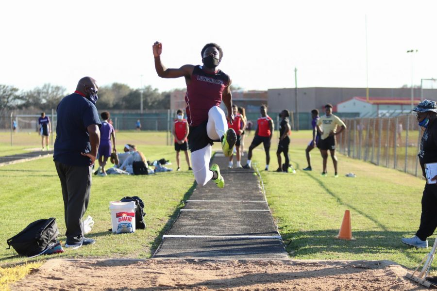 Ademola Bello (11) was soaring through the air trying to beat his PR for the long jump.