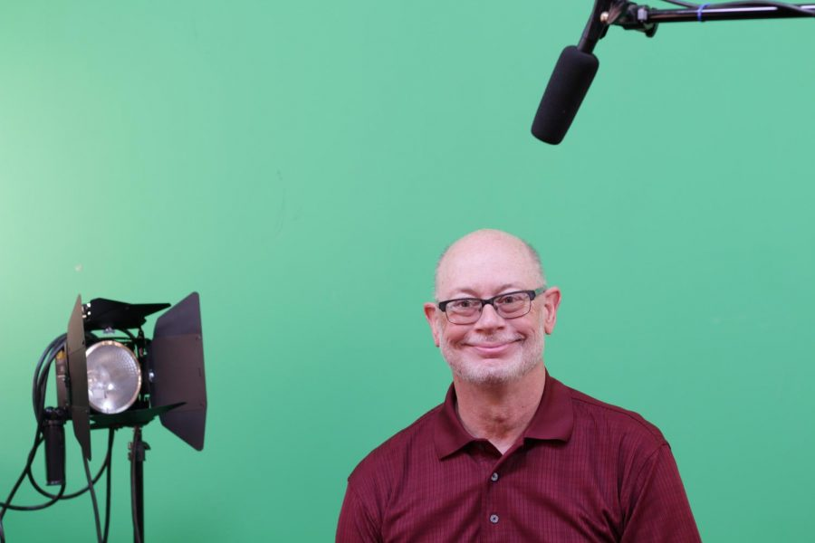 Mr. Terrando sitting in his studio in front of his green screen that his students use to create the student news.