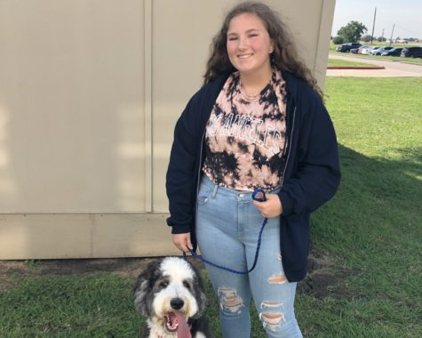 Kassandra Kee stands with Scout one of the classroom dogs in her Animal Science Class.